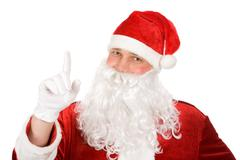 Photo of happy santa claus keeping his forefinger stuck upwards Stock Photos