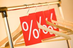 Image of several wooden hangers with red labels showing discount on them Stock Photos