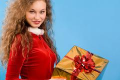 Portrait of pretty smiling girl with giftbox over blue background Stock Photos