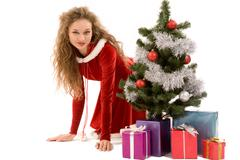Portrait of pretty smiling girl with giftboxes and decorated xmas tree near by Stock Photos