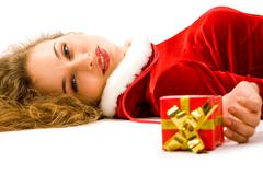 photo of pretty smiling girl lying with small giftbox in hand - stock photo