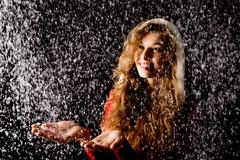 portrait of pretty girl with open palms catching falling snow over dark backgrou - stock photo