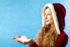 Portrait of pretty girl with snow on her palms over blue background Stock Photos