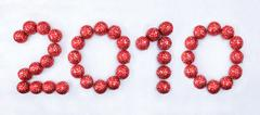 image of 2010 number made up of red decorative toy balls on the snow - stock photo