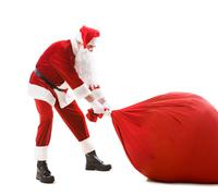 portrait of happy santa carrying heavy big red sack with presents - stock photo