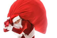 portrait of strong santa claus holding big red sack and looking at camera - stock photo