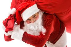 portrait of strong santa claus with big red sack looking at camera - stock photo