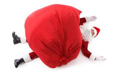 photo of tired santa claus with big red sack on his top - stock photo