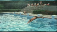 Vintage 8 mm film: Man jumps from springboard, 1970s Stock Footage