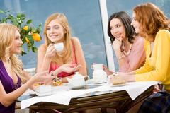 portrait of four attractive women having lunch and discussing - stock photo