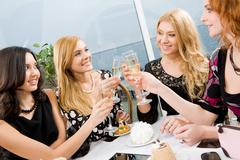 portrait of elegantly ladies with champagne touching their glasses - stock photo