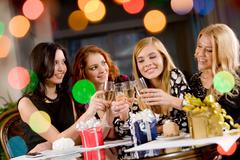 portrait of attractive women clinking champagnes with each other during hen-part - stock photo