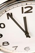 Close-up of clock showing five minutes to twelve Stock Photos