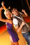 positive couple dancing at disco and looking at camera - stock photo