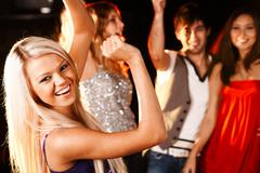 portrait of cheerful girl dancing at party with her friends behind - stock photo