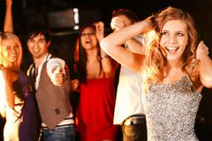 Portrait of joyous girl dancing at party with her friends behind Stock Photos
