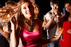 portrait of cheerful girl with cocktail in hand having fun at discotheque - stock photo