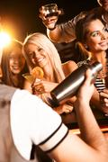 photo of pretty girls toasting and looking at barman - stock photo