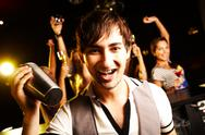 Stock Photo of portrait of smiling male with bottle looking at on background of dancers