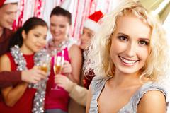 face of pretty girl looking at camera with smile on background of her friends pa - stock photo