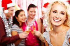Face of pretty girl looking at camera with smile on background of her friends pa Stock Photos