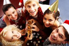 View from above of merry friends with flutes of champagne looking upwards Stock Photos