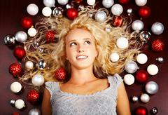 Creative image of lying blond girl with lots of decorative balls on ends of her Stock Photos