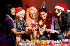 Portrait of laughing friends enjoying xmas lights at new year party Stock Photos