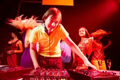 portrait of handsome deejay looking at camera with dancing teens on background - stock photo