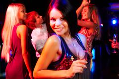 portrait of happy dancer looking at camera on background of her friends - stock photo