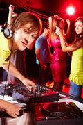 smart deejay looking at camera with dancing teens on background - stock photo