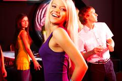 image of energetic girl looking at camera while dancing on background of her fri - stock photo