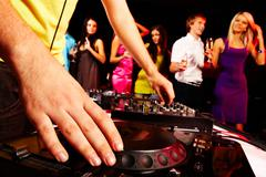 Close-up of human hand spinning turntable with group of dancers on background Stock Photos