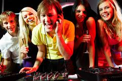Portrait of handsome deejay singing with joyful friends near by Stock Photos