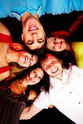 below angle of group of friends embracing each other and looking at camera - stock photo