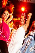 portrait of smart dancers moving at disco while raising their arms - stock photo