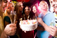 Portrait of seven persons holding glasses around cake with lights Stock Photos