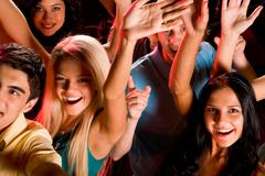 close-up of joyful friends raising their hands smiling at discotheque - stock photo
