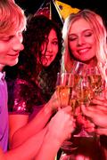 Stock Photo of vertical image of three friends clinking glasses with each other during birthday