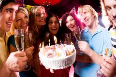 portrait of friends holding cocktails around festive cake during birthday - stock photo