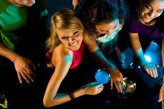 Above angle of happy girl looking at camera with her friends near by in the bar Stock Photos