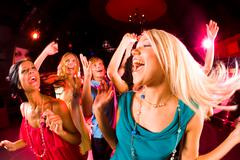 Portrait of cheerful girl dancing at party with her friends on background Stock Photos