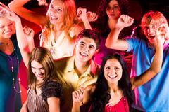 Joyful teens enjoying themselves in night club while dancing Stock Photos