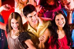 joyful teens enjoying themselves in night club while dancing - stock photo