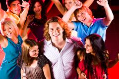 Portrait of happy guy embracing two smart girls in night club at party with thei Stock Photos