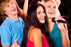 Photo of pretty girls with microphone singing in it and friendly guy behind them Stock Photos