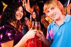 portrait of happy couple with flutes of champagne toasting at birthday party - stock photo