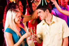 Portrait of happy couple with flutes of champagne with their friends on backgrou Stock Photos