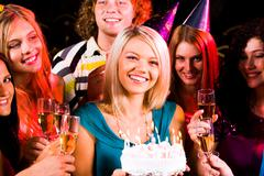 portrait of joyful girl holding birthday cake surrounded by friends with flutes - stock photo
