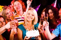 Portrait of joyful girl holding birthday cake surrounded by friends at party Stock Photos